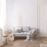 Blanket and pillows on wooden sofa in white loft interior with pouf and plant on carpet. Real photo